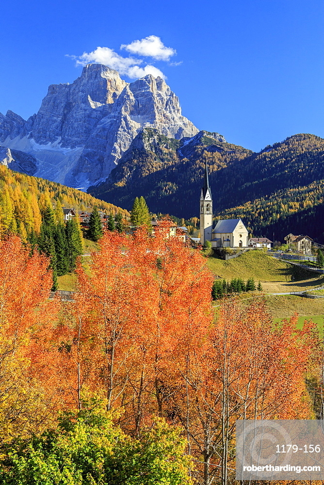 Red and orange trees in front of the tiny church of Selva di Cadore, in the Dolomites, with Mount Pelmo in the background, Veneto, Italy, Europe