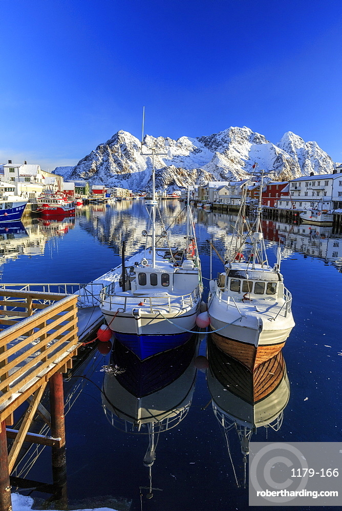 Boats docked in the calm waters of the port of Henningsvaer with the Norwegian Alps in the background, Lofoten Islands, Arctic, Norway, Scandinavia, Europe
