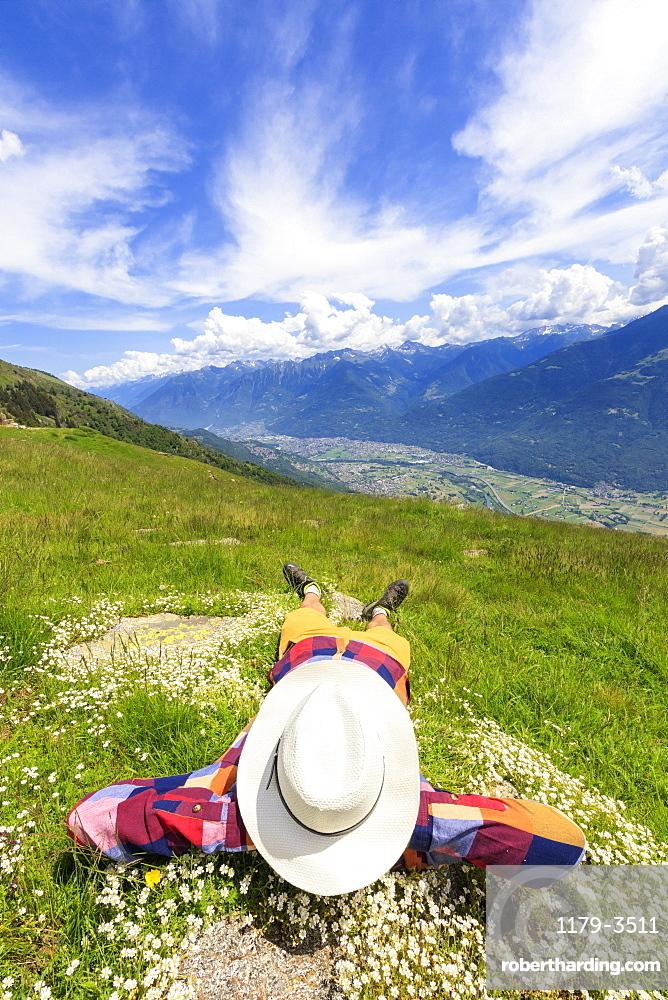Rear view of man with hat lying on grass, Alpe Bassetta, Valtellina, Sondrio, Lombardy, Italy, Europe