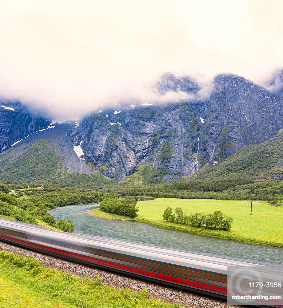 The Rauma Line express train runs beside the river in Romsdalen Valley, Andalsnes, More og Romsdal county, Norway