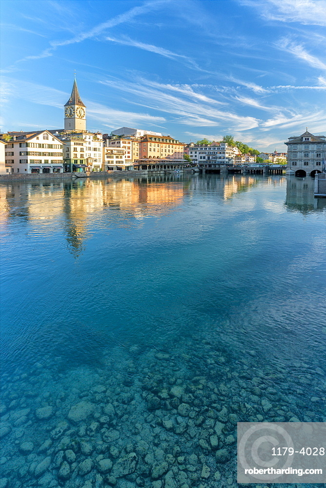 Clock tower of St.Peter church mirrored in the turquoise water of Limmat River, Lindenhof, Zurich, Switzerland