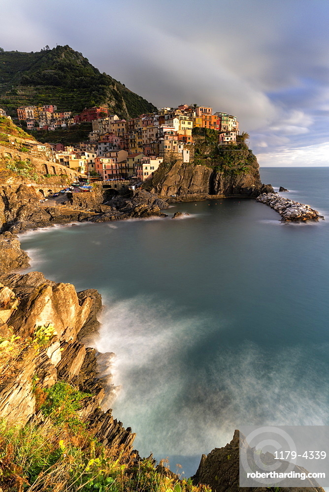 Waves crashing on cliffs next to Manarola, Cinque Terre, La Spezia province, Liguria, Italy