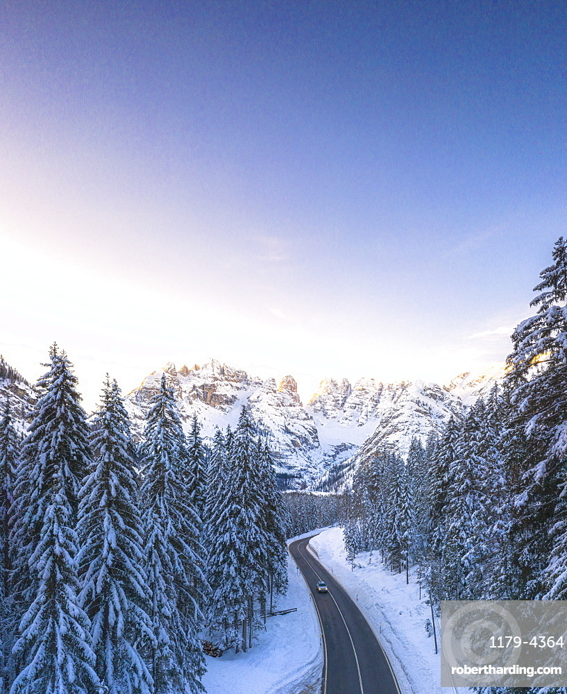 Car traveling on the scenic road Dobbiaco-Misurina along snowy woods at dawn, aerial view, Dolomites, South Tyrol, Italy (drone)