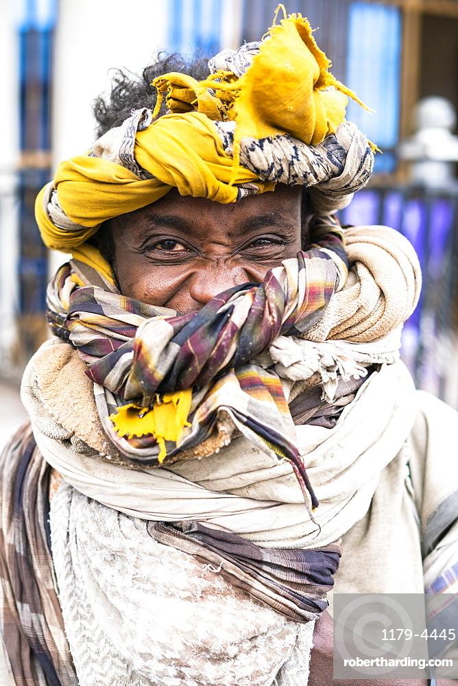 Portrait of young man with headwrap smiling at camera, Bati, Amhara Region, Oromia, Ethiopia, Africa