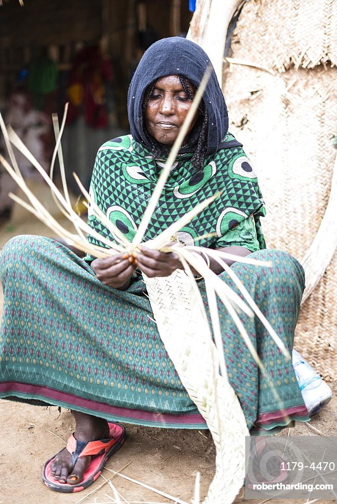 Elderly woman working with straw in Melabday village, Asso Bhole, Dallol, Danakil Depression, Afar Region, Ethiopia, Africa