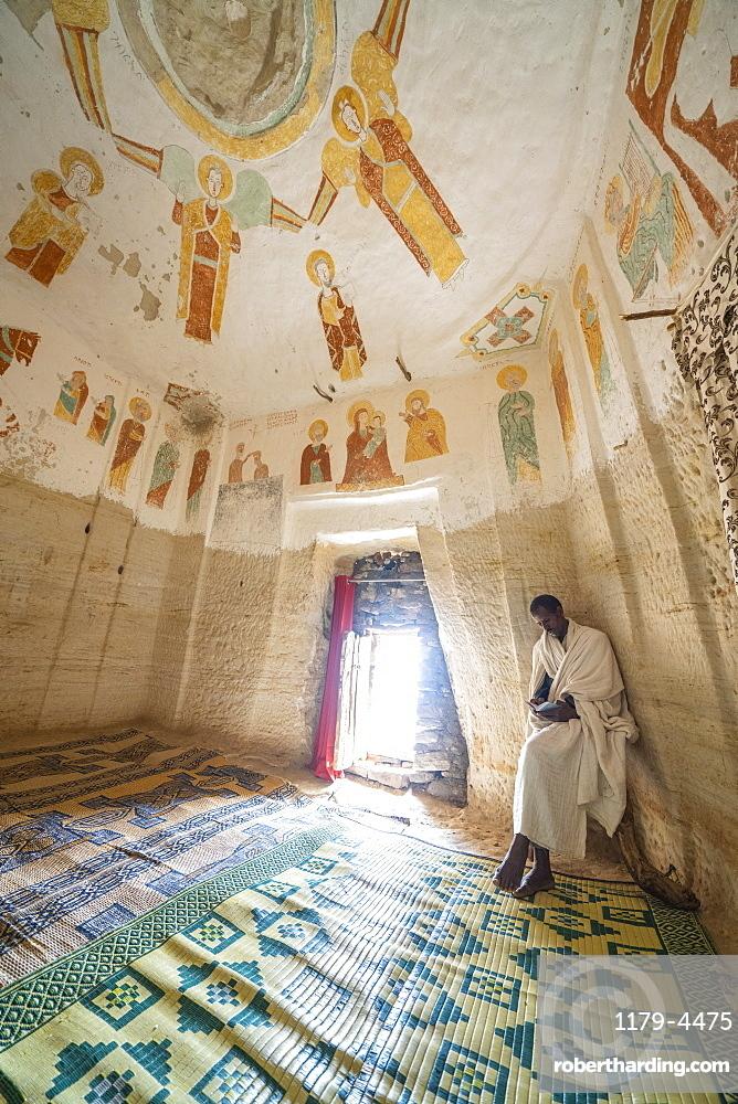 Orthodox priest holding a holy book inside Daniel Korkor church, Gheralta Mountains, Tigray Region, Ethiopia, Africa