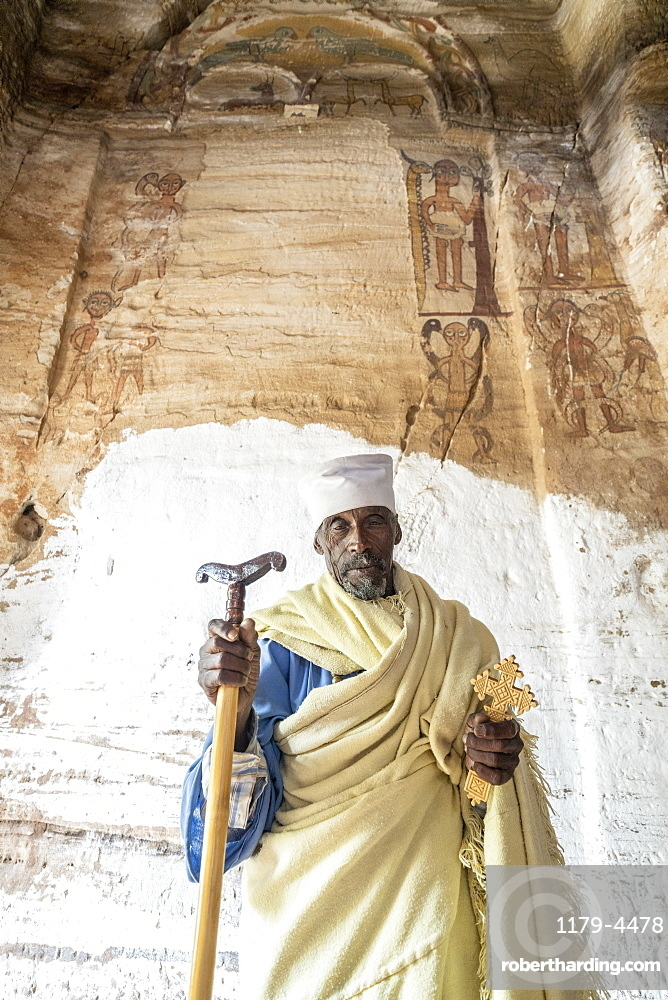 Orthodox priest holding the hand cross and prayer stick in Maryam Korkor church, Gheralta Mountains, Tigray Region, Ethiopia