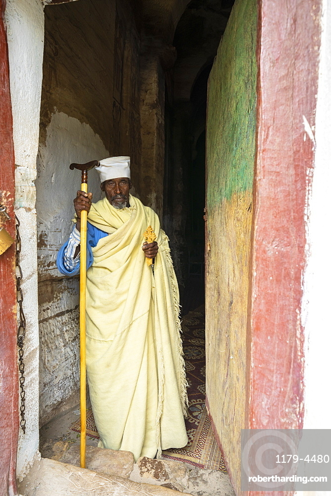 Orthodox priest holding the hand cross at the entrance of Maryam Korkor church, Gheralta Mountains, Tigray Region, Ethiopia