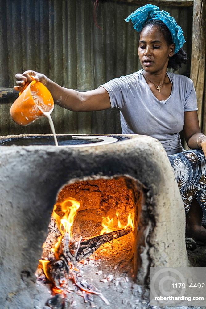 Woman making injera bread on traditional oven, Berhale, Afar Region, Ethiopia, Africa