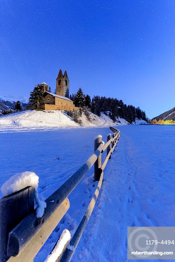 Wood fence in the snow surrounding the church of San Gian, Celerina, St. Moritz, canton of Graubunden, Engadine, Switzerland
