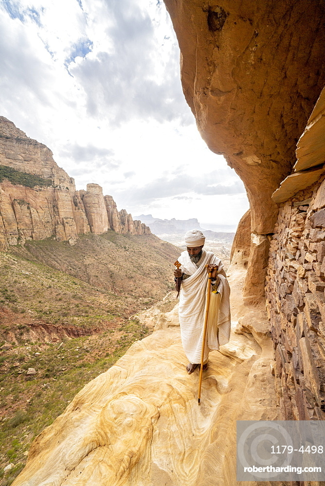 Priest holding the hand cross on rocks outside Abuna Yemata Guh church, Gheralta Mountains, Tigray Region, Ethiopia, Africa