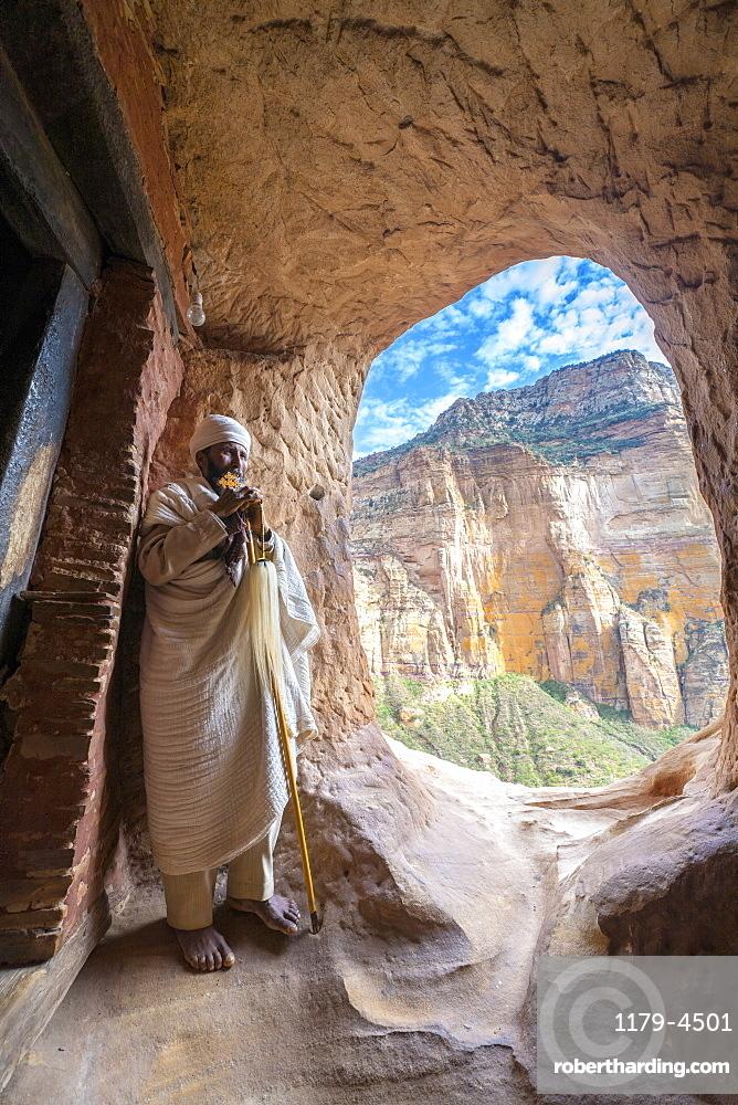 Ethiopian orthodox priest holding the hand cross at entrance of Abuna Yemata Guh church, Gheralta Mountains,Tigray, Ethiopia