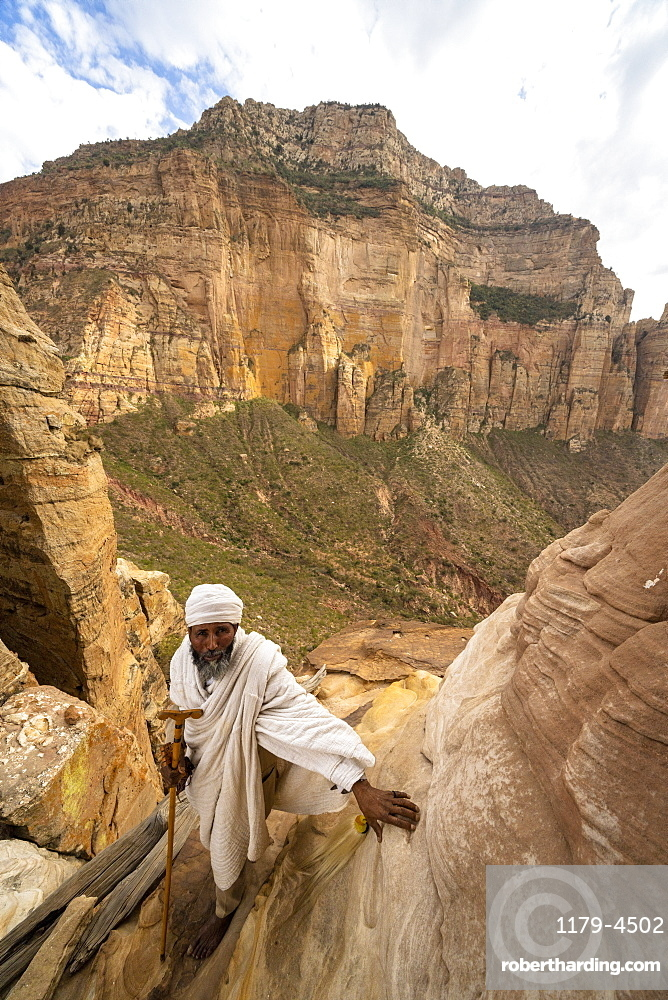 Ethiopian priest leaning on steep rocks leading to Abuna Yemata Guh church, Gheralta Mountains,Tigray Region, Ethiopia
