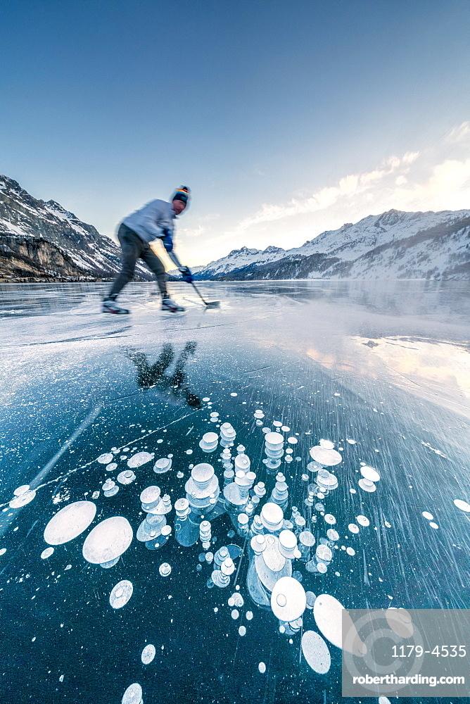 Man playing ice hockey on frozen Lake Sils, canton of Graubunden, Engadine, Switzerland