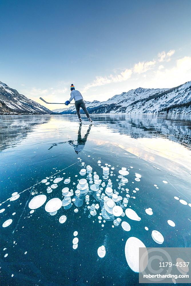 Ice hockey player skating on frozen Lake Sils covered of bubbles, canton of Graubunden, Engadine, Switzerland