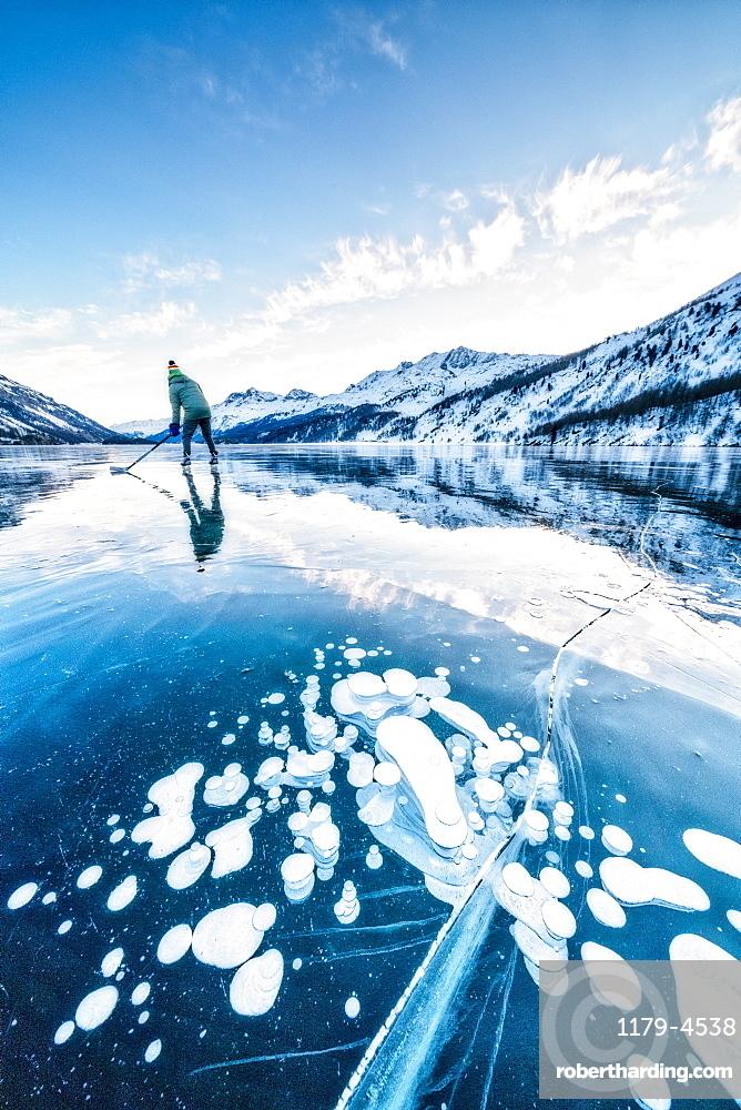 Man playing ice hockey on frozen Lake Sils covered of bubbles, canton of Graubunden, Engadine, Switzerland