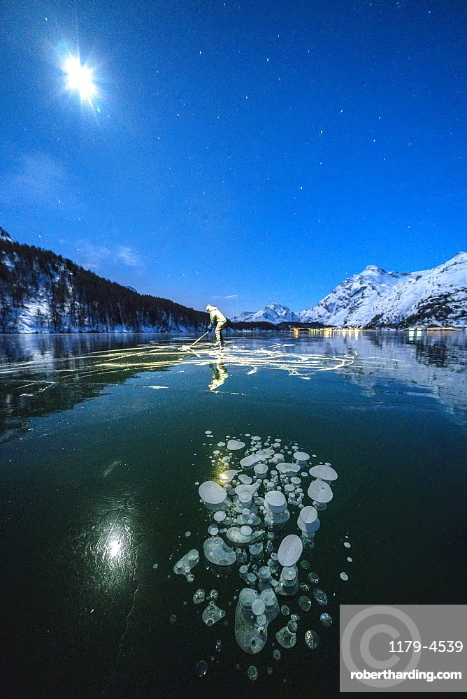 Full moon on ice skater on frozen Lake Sils lit by head torch, canton of Graubunden, Engadine, Switzerland