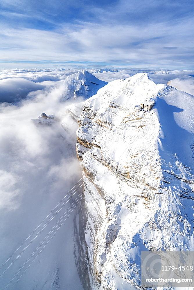 Aerial view of snow capped Tofane group and scenic Freccia nel Cielo cableway, Dolomites, Belluno province, Veneto, Italy