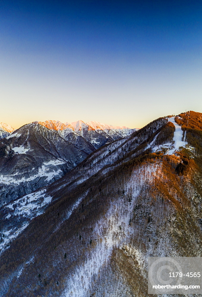 Ski slopes of Pian Delle Betulle and Alpe Paglio lit by sunset, aerial view, Valsassina, Lecco province, Lombardy, Italy (drone)