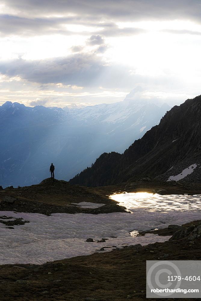 Silhouette of man standing under sun rays at dawn on shores of lake Zana, Valmalenco, Valtellina, Lombardy, Italy