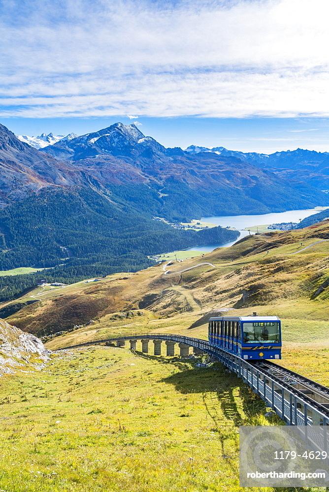 Chantarella-Corviglia funicular traveling uphill with St. Moritz lake on background, Engadine, canton of Graubunden, Switzerland
