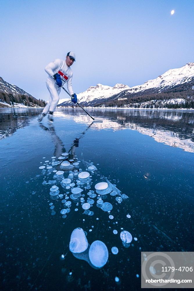 Ice hockey player man skating on Lake Sils covered of ice bubbles at dusk, canton of Graubunden, Engadine, Switzerland