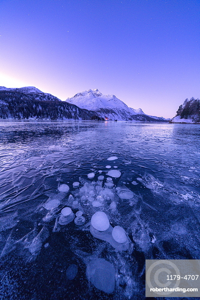 Ice bubbles trapped in Lake Sils with Piz Da La Margna in background at dawn, Graubunden canton, Engadine, Switzerland