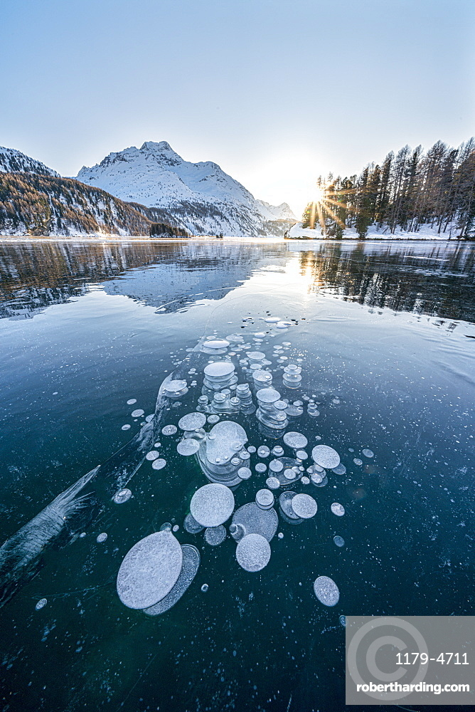 Ice bubbles trapped in frozen Lake Sils at sunset with Piz Da La Margna in background, Graubunden canton, Engadine, Switzerland
