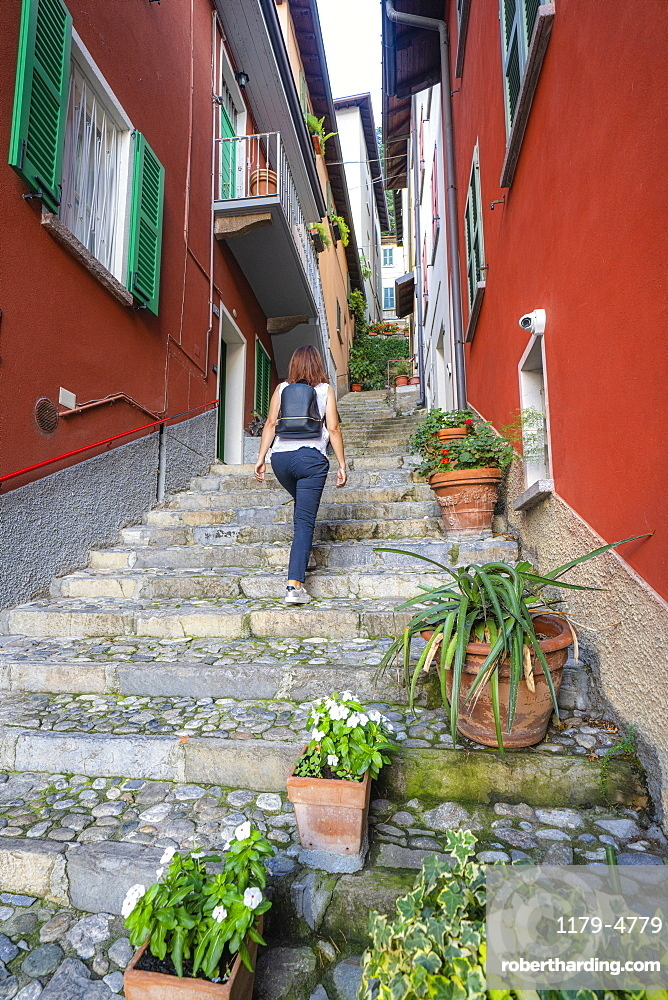 Rear view of woman walking on flight of steps in the old alley of Varenna, Lake Como, Lecco province, Lombardy, Italy
