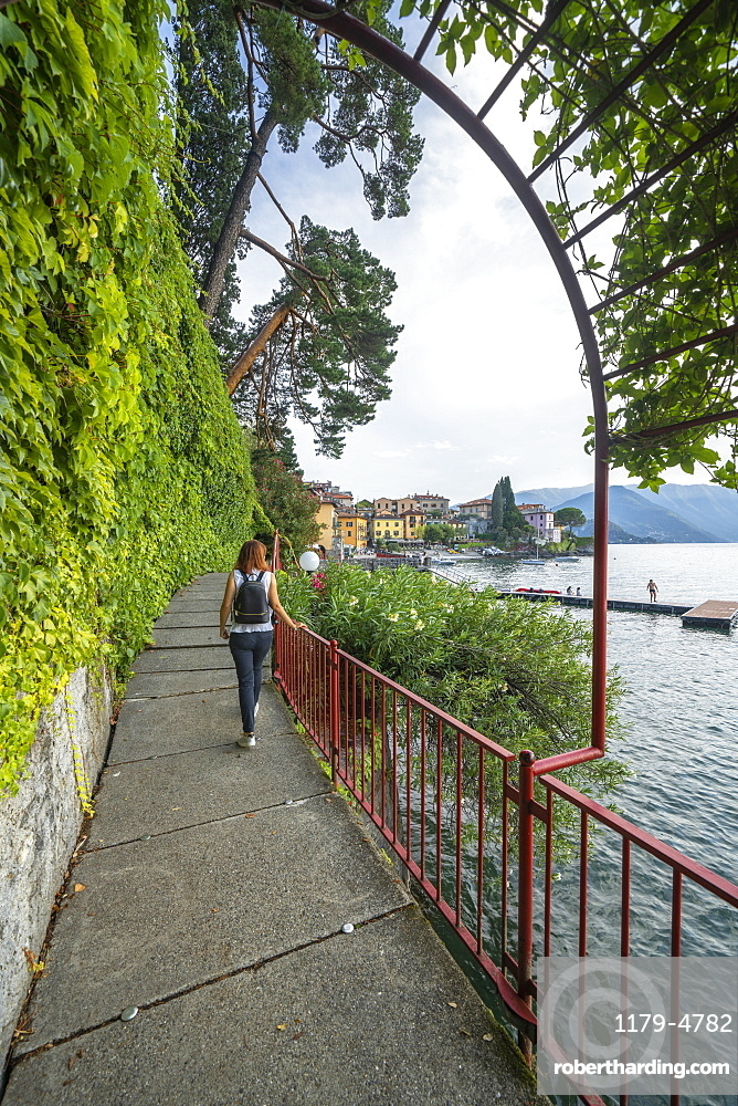 Woman walking on famous lovers' promenade on lakeside of Varenna, Lake Como, Lecco province, Lombardy, Italy