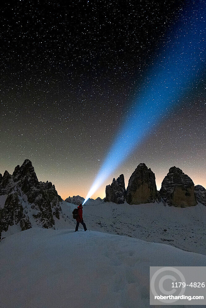 Hiker with head torch admiring stars on Monte Paterno and Tre Cime di Lavaredo, Sesto Dolomites, South Tyrol, Italy