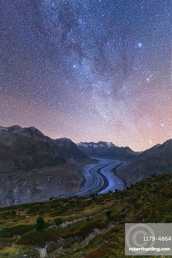 Glowing stars and Milky Way in the night sky over Aletsch Glacier, Bernese Alps, Valais canton, Switzerland
