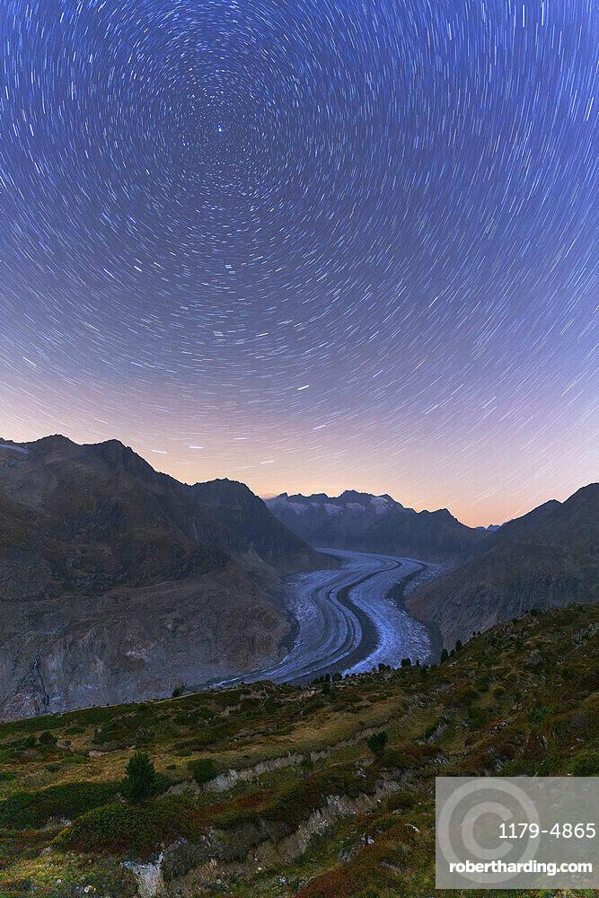 Star trail in the night sky above Aletsch Glacier, Bernese Alps, Valais canton, Switzerland