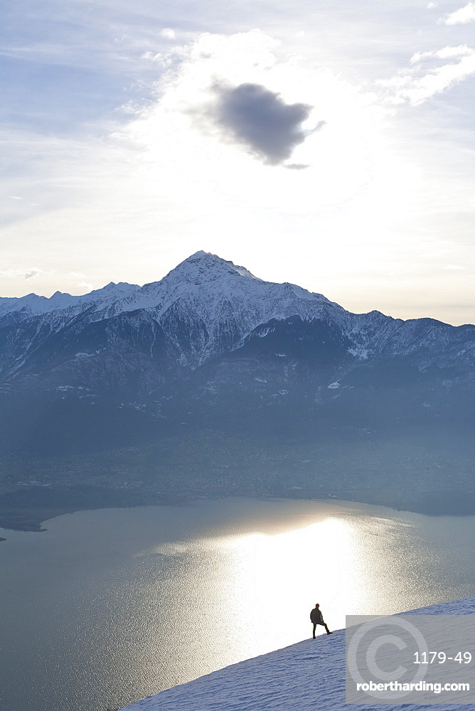Silhoutte of a hiker facing Mount Legnone and Lake Como at sunset, Lombardy, Italy, Europe