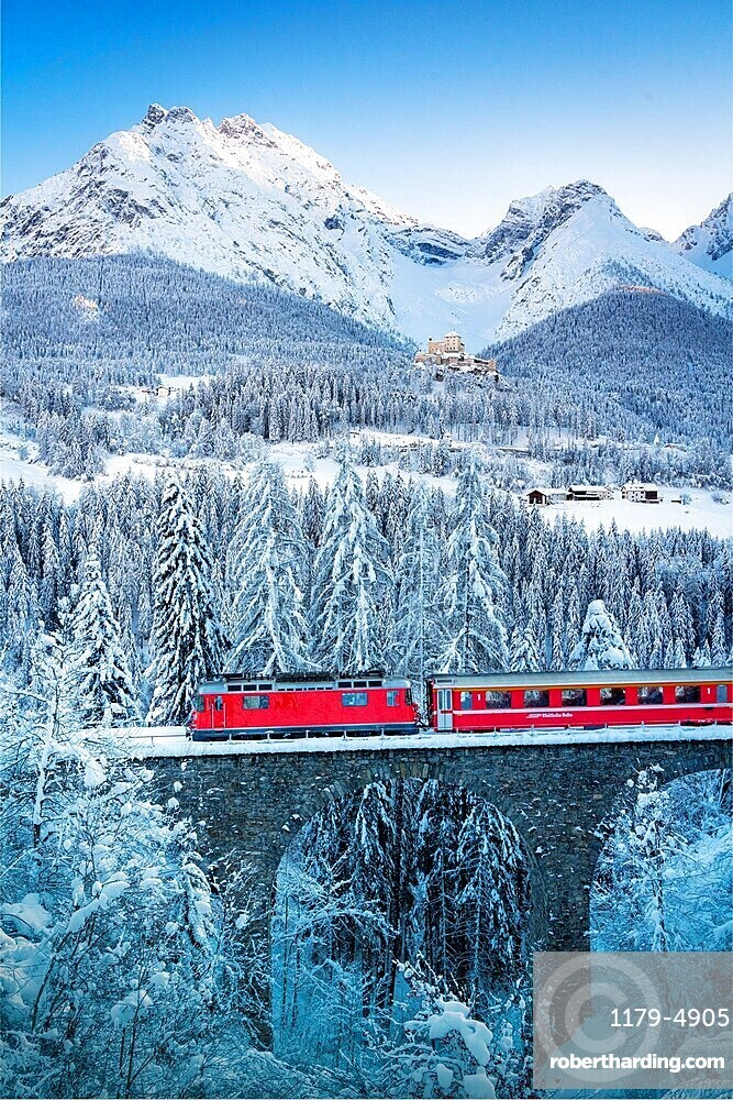 Bernina Express train in the winter forest covered with snow surrounding Tarasp Castle, Graubunden canton, Engadin, Switzerland