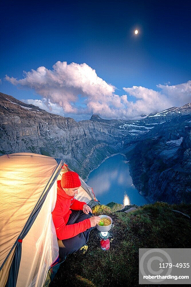 Hiker man cooking while camping in a tent above lake Limmernsee, Canton of Glarus, Switzerland