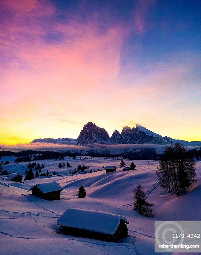 Mountain huts covered with snow at dawn whit Sassopiatto and Sassolungo on background, Seiser Alm, Dolomites, South Tyrol, Italy
