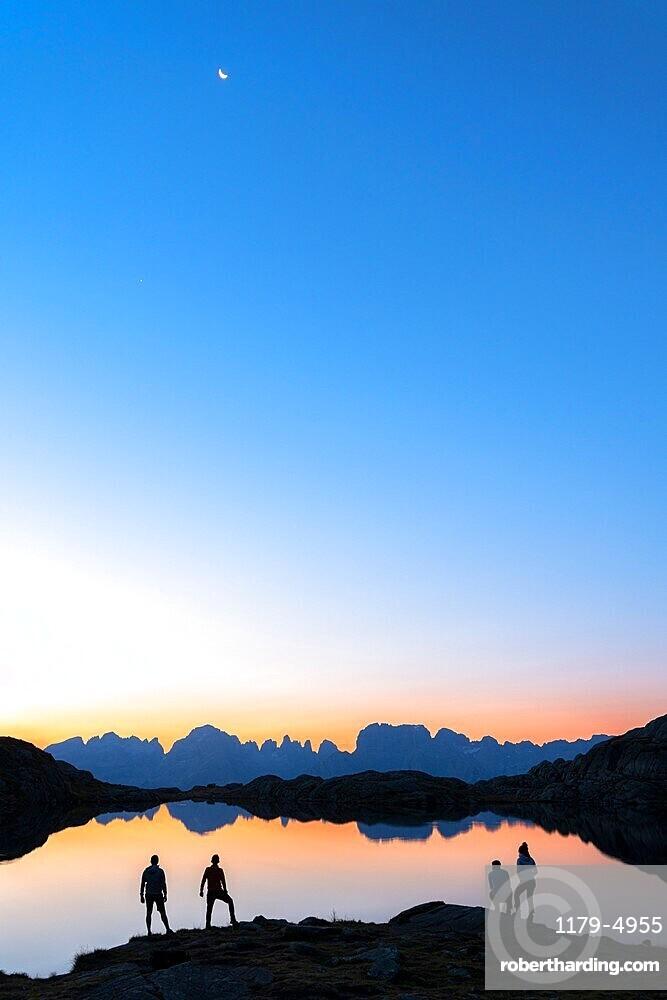 Hikers admiring Brenta Group Dolomites reflected in Lago Nero di Cornisello at dawn, Trento,Trentino-Alto Adige, Italy