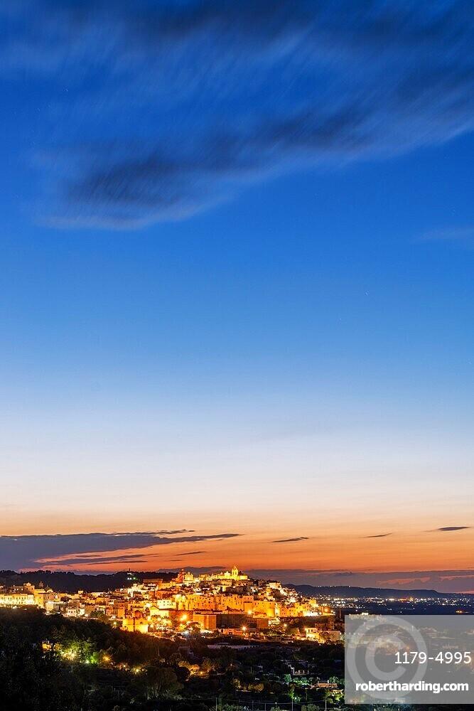Illuminated old town of Ostuni at dusk, province of Brindisi, Salento, Apulia, Italy, Europe