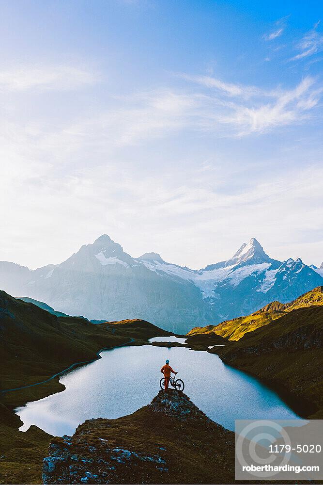 Mountain biker looking at Bachalpsee lake and Bernese Oberland mountains at dawn, Grindelwald, Bern Canton, Switzerland, Europe