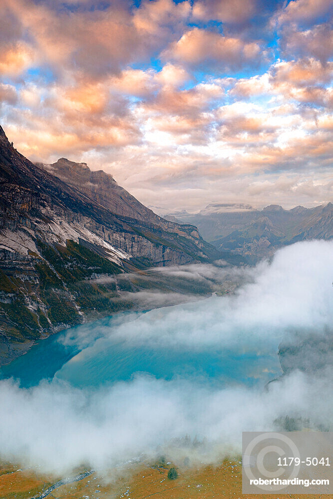 Clouds at sunset over the pristine lake Oeschinensee in the mist, Bernese Oberland, Kandersteg, canton of Bern, Switzerland, Europe