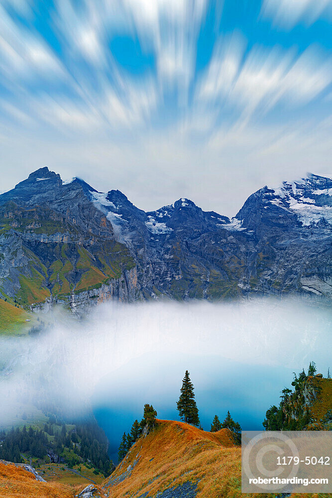 Clouds in the sky above lake Oeschinensee covered by fog, Bernese Oberland, Kandersteg, canton of Bern, Switzerland, Europe