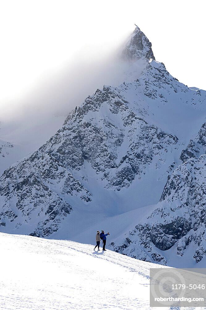 Tourists photographing the snowy peaks during a winter hike, Muottas Muragl, Samedan, Engadine, Graubunden canton, Switzerland, Europe