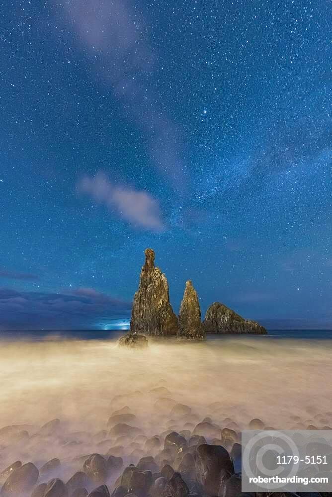 Waves crashing over Ilheus da Rib and Ribeira da Janela rock formations under the starry night sky, Madeira, Portugal