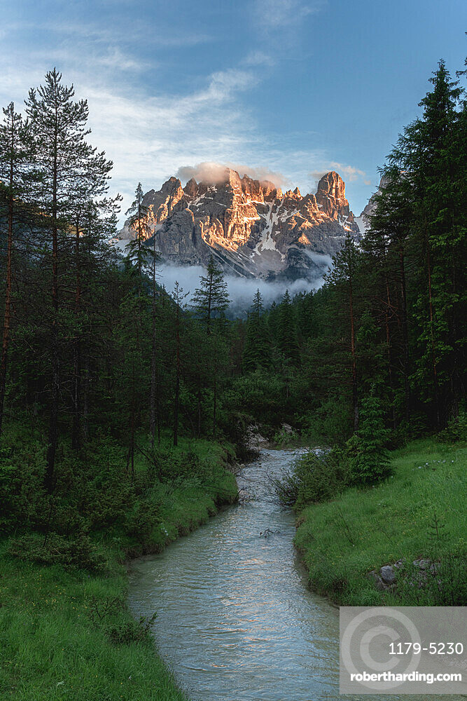 River in the green valley with Cristallo and Popena group on background at sunset, Dolomites, South Tyrol, Italy