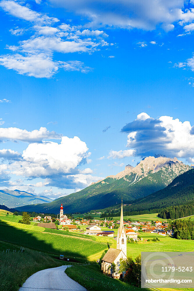 Sunshine over green pastures and village of Villabassa /Niederdorf in summer, Val Pusteria, Bolzano province, South Tyrol, Italy