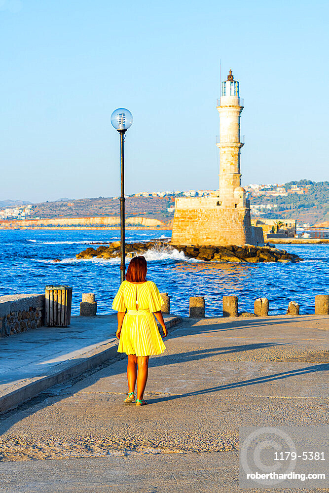 Charming woman with dress walking to the old lighthouse at sunset, Chania, Greece