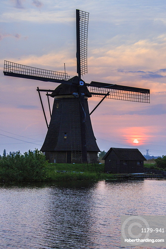 Blue sky and pink clouds on the windmill reflected in the canal at dawn, Kinderdijk, Rotterdam, South Holland, Netherlands, Europe
