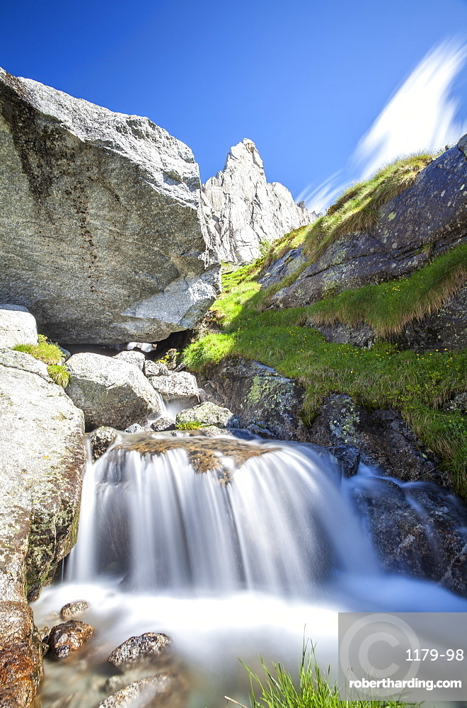 The granite peak of a mountain in Valmasino, famous among climbers, contrasting with the flowing waters of a stream, Lombardy, Italy, Europe