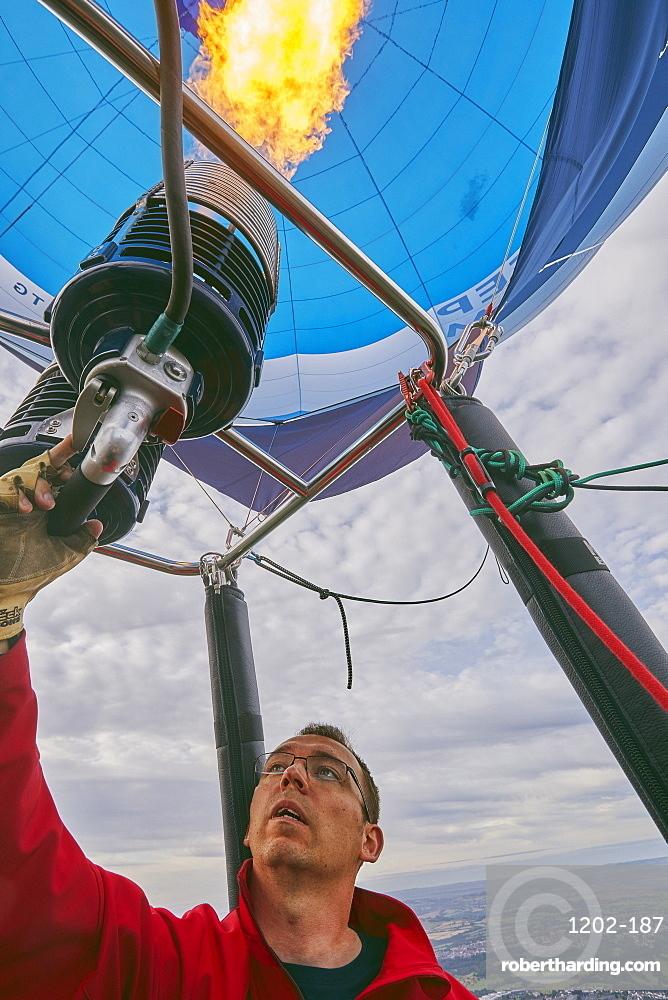 A balloon pilot adjusting the burning gas jets that heat air inside the balloon, during the Bristol International Balloon Fiesta, England, United Kingdom, Europe